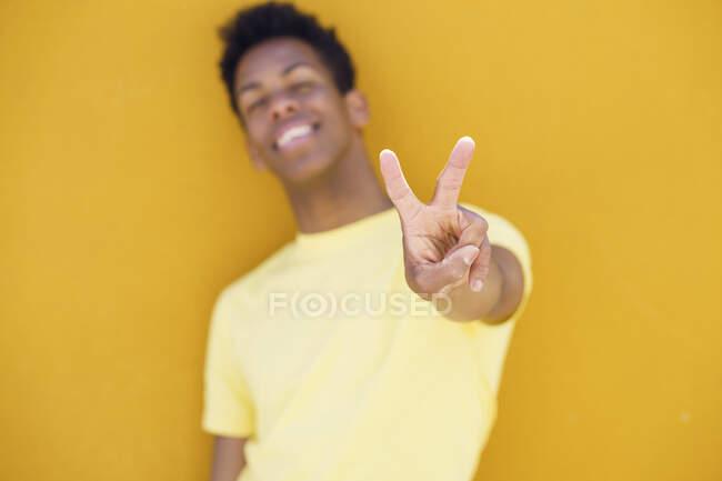 Hombre sonriente mostrando gesto de paz frente a la pared amarilla - foto de stock