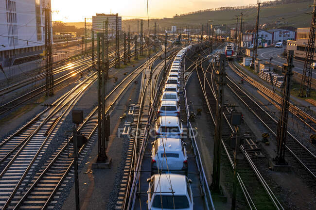 Германия, Бавария, Вурцбург, Ряд вагонов, перевозимых по городским железнодорожным путям на закате — стоковое фото