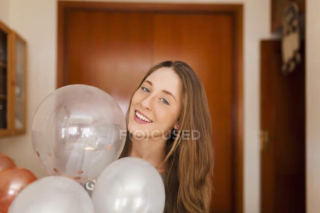 Mujer con globos en casa - foto de stock