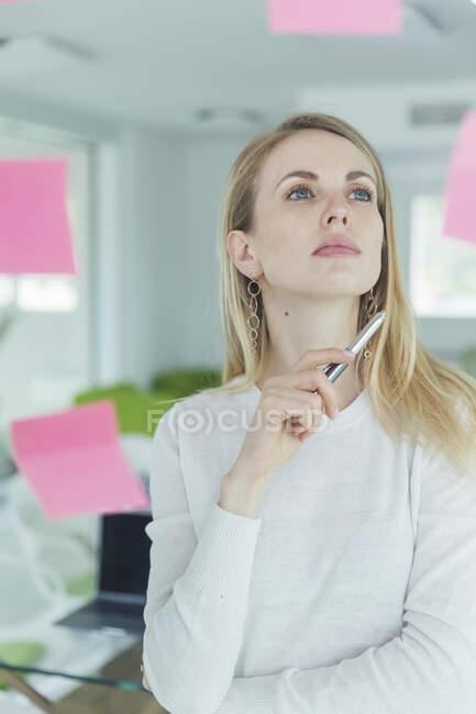 Empresária atenciosa olhando para nota adesiva no escritório — Fotografia de Stock