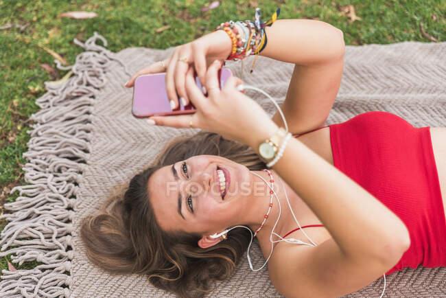 Mujer feliz escuchando música a través de auriculares mientras usa el teléfono inteligente en la manta en el parque - foto de stock