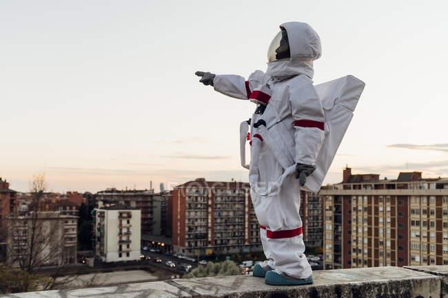 Женщина-астронавт в скафандре, указывающая на удерживающую стену во время заката — стоковое фото