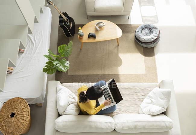 Жінка за допомогою ноутбука сидить на дивані у вітальні. — стокове фото