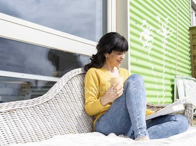Женщина с книгой чтения кружки, сидя на диване на балконе — стоковое фото
