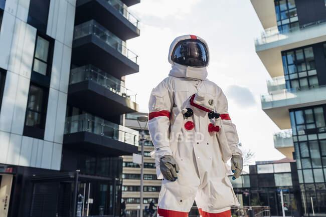 Male astronaut wearing space helmet standing amidst buildings - foto de stock