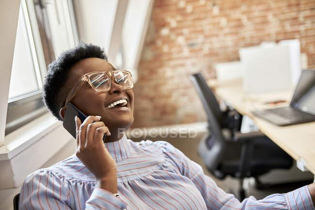 Empresária feliz usando óculos falando no telefone inteligente no escritório — Fotografia de Stock