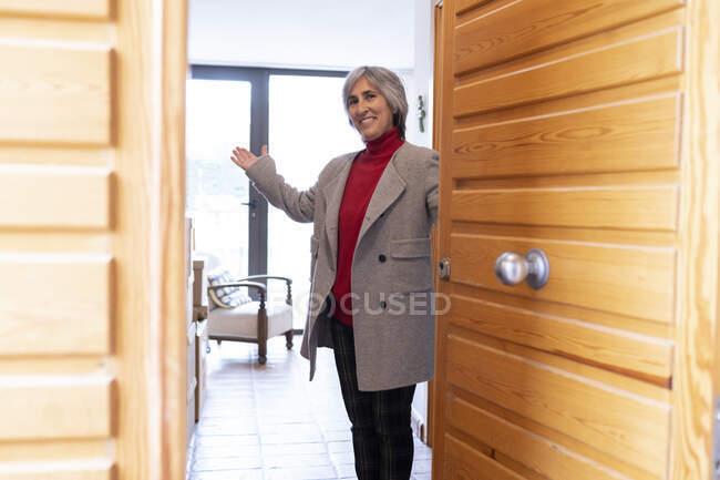 Mujer sonriente dando la bienvenida a los huéspedes en la puerta principal de la casa - foto de stock