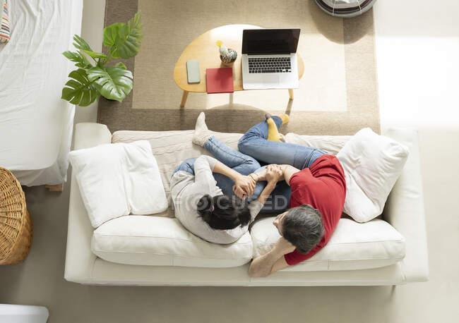 Сердечна пара обіймає одне одного, сидячи на дивані у вітальні. — стокове фото