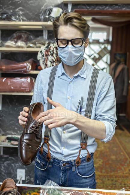 Profissional masculino com máscara protetora segurando sapato na loja durante COVID-19 — Fotografia de Stock