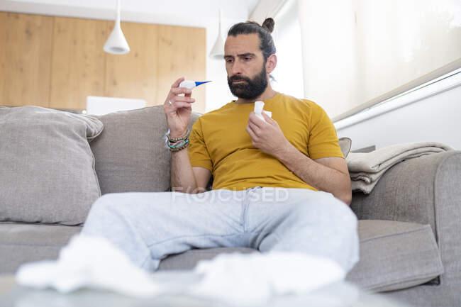 Hombre maduro comprobando la temperatura corporal a través del termómetro en casa - foto de stock
