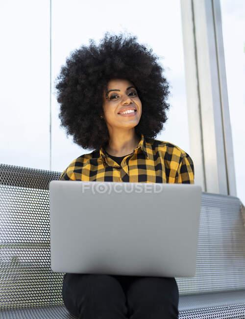 Посмішка молодої жінки з лептопом сидячи на лавці. — стокове фото