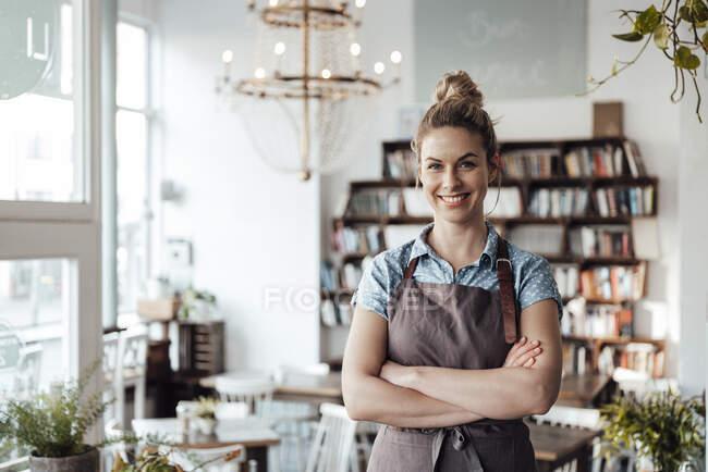 Впевнена офіціантка середнього віку стоїть зі схрещеними руками в кав'ярні. — стокове фото