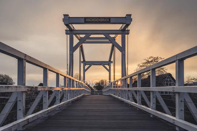 Alemania, Altes Land, Hogendiekbrucke pasarela de madera al atardecer - foto de stock