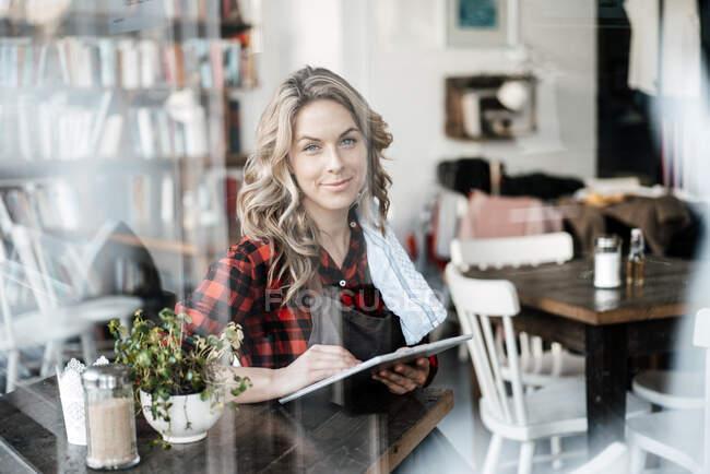 Серед дорослої жінки, яка сиділа біля вікна кафе. — стокове фото