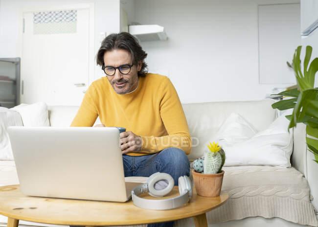 Чоловік з окулярами дивиться на ноутбук, сидячи на дивані у вітальні. — стокове фото