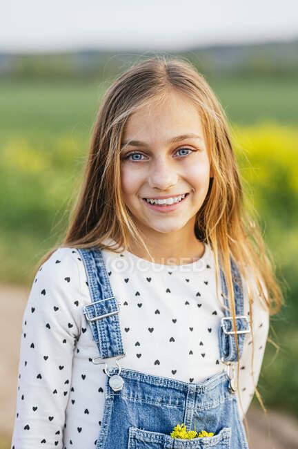 Sorridente ragazza bionda in piedi al campo agricolo — Foto stock