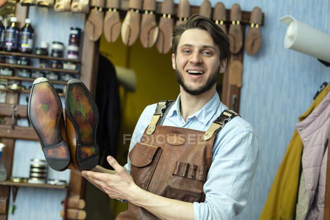 Sorrindo sapateiro masculino mostrando sola de sapato na oficina — Fotografia de Stock