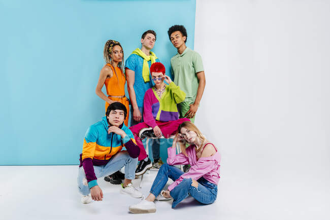Stylish male and female friends in colorful clothes looking at camera — Stock Photo
