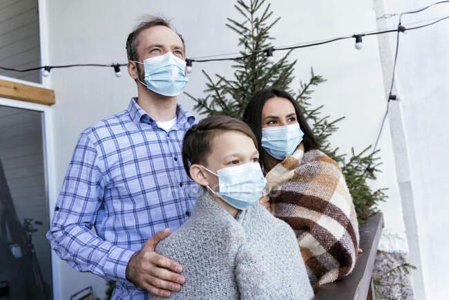 Familia con mascarillas protectoras mirando hacia otro lado en el balcón durante la pandemia - foto de stock