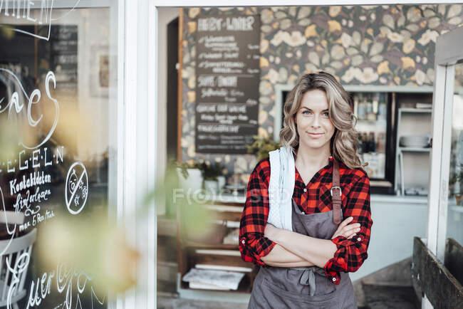 Впевнена жінка-підприємець стоїть зі зброєю, схрещеною біля входу в кафе. — стокове фото