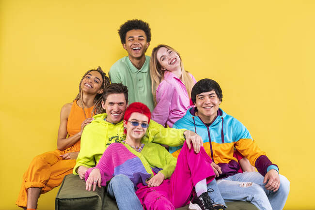Friends smiling while sitting together in front of yellow background — Stock Photo
