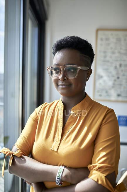 Довірлива жінка-професіонал, яка відвернулася, стоячи біля вікна в офісі — стокове фото