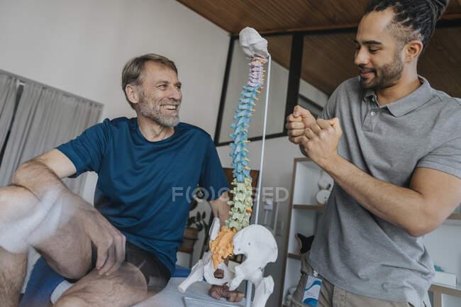 Paciente masculino sonriente mirando al fisioterapeuta haciendo gestos por modelo de columna vertebral en la práctica - foto de stock