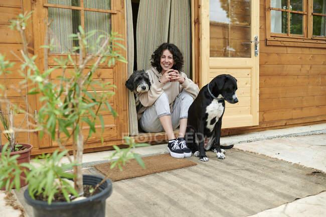 Mujer feliz sentada en medio de perros en la puerta - foto de stock