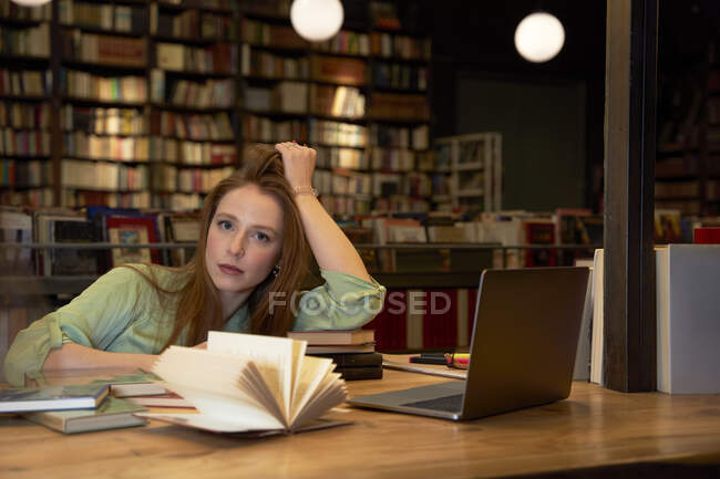 Mulher séria com a mão no cabelo sentado na biblioteca — Fotografia de Stock