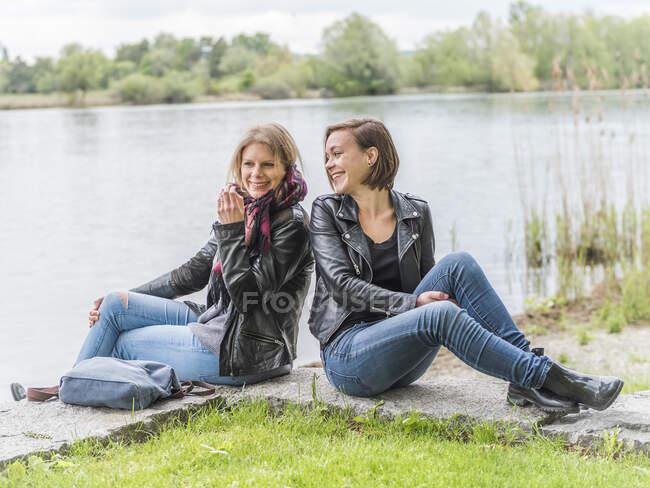Dois amigos sorridentes sentados perto da água se divertindo — Fotografia de Stock