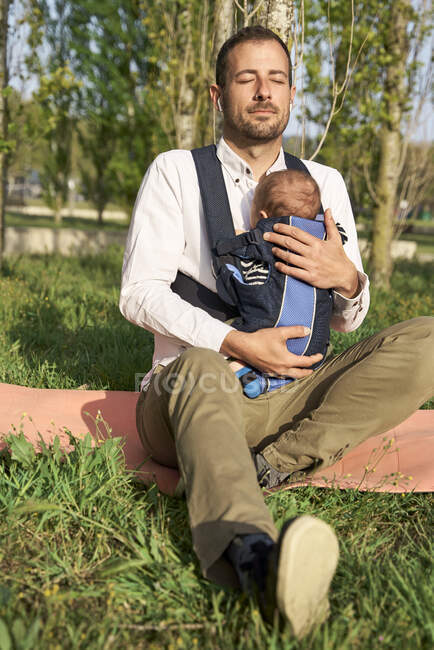 Man sitting with baby at park during sunny day — Stock Photo