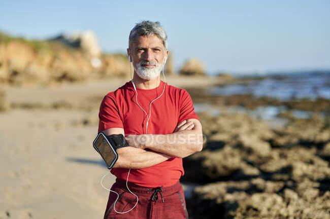 Довірливий чоловік зі схрещеними руками стоїть на пляжі в сонячний день. — стокове фото