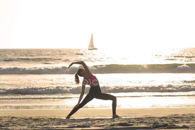 Молодая женщина вытягивает руки на берегу на пляже в солнечный день — стоковое фото