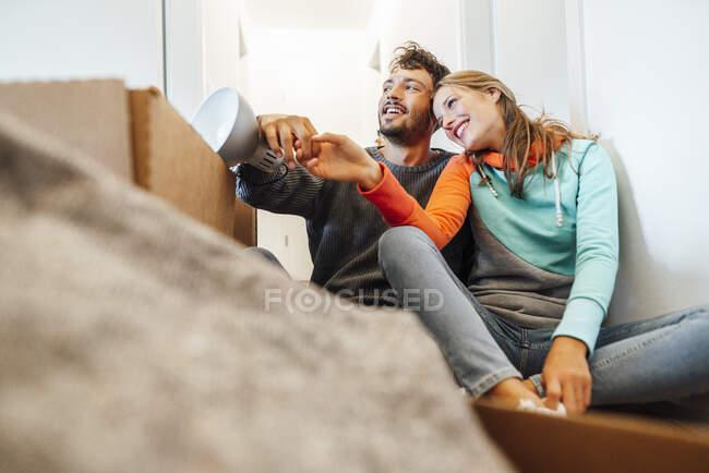 Feliz pareja joven sentados juntos mientras miran hacia otro lado - foto de stock
