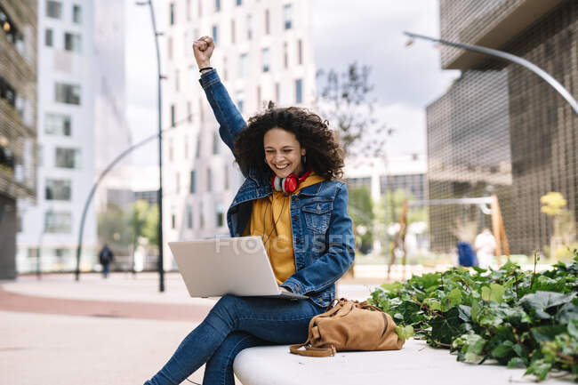 Mujer joven animando mientras usa el ordenador portátil en la ciudad - foto de stock