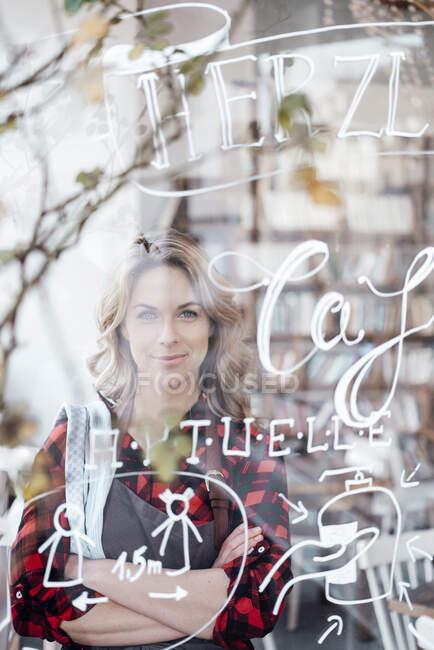 Mujer de negocios adulta con los brazos cruzados de pie en la cafetería - foto de stock