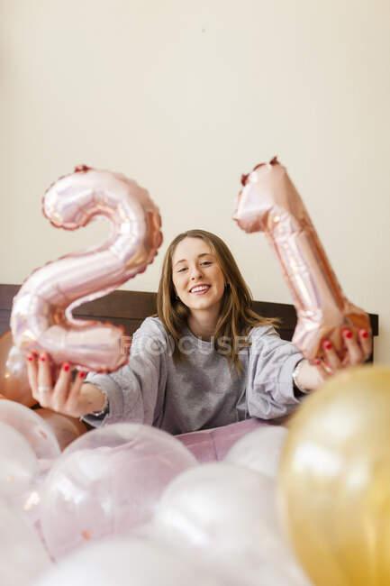 Mujer sonriente sosteniendo globos de helio número 21 mientras está sentada en la cama en casa - foto de stock