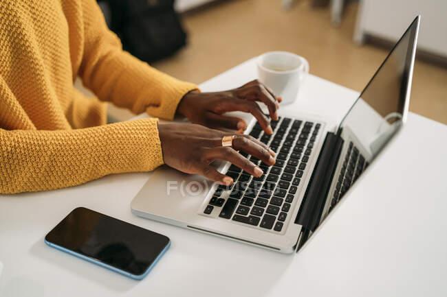 Jeune femme tapant tout en utilisant un ordinateur portable à la maison — Photo de stock