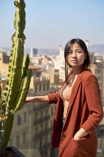Mujer de pie con las manos en los bolsillos en la terraza - foto de stock
