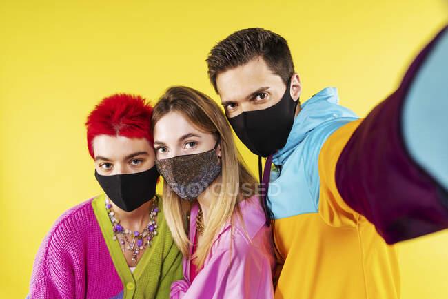 Amigos de moda con máscara facial tomando selfie a través del teléfono móvil en frente de fondo amarillo - foto de stock