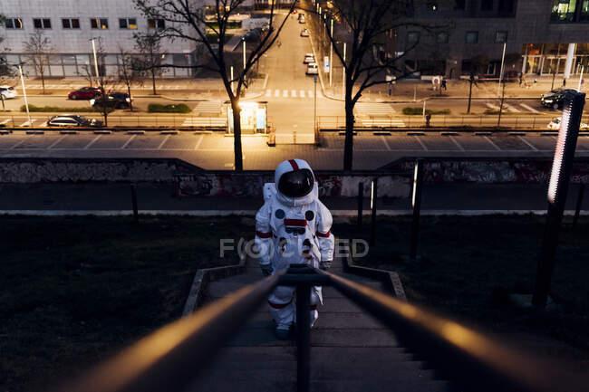 Astronauta de pie en la escalera cerca de la carretera por la noche - foto de stock