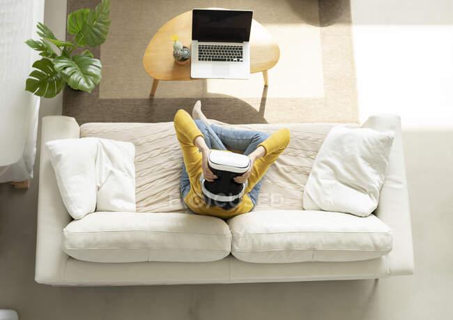 Женщина, держащая гарнитуру виртуальной реальности, сидя дома на диване — стоковое фото