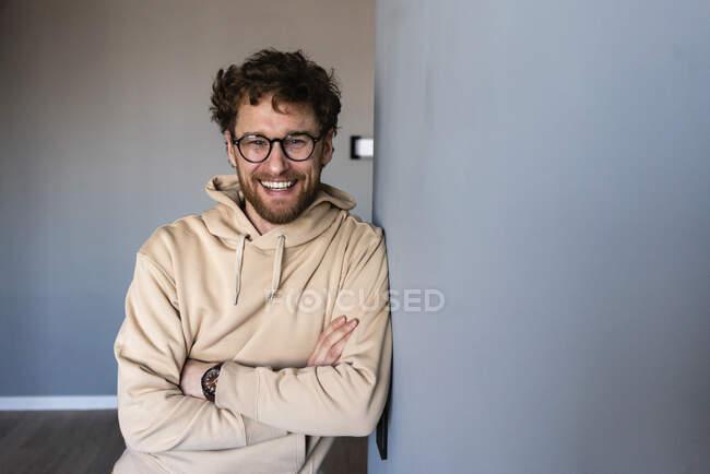 Усміхнений чоловік у окулярах, спираючись на стіну з перехрещеними руками. — стокове фото