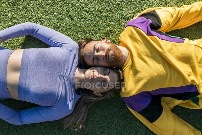 Pareja descansando mientras está acostado en la hierba durante el día soleado - foto de stock