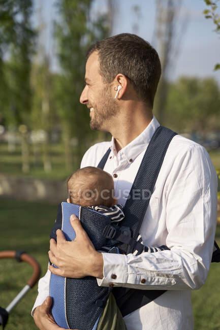 Hombre adulto medio con hijo en portabebés en día soleado - foto de stock