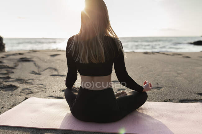 Женщина, занимающаяся йогой на пляже — стоковое фото
