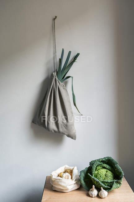Verduras en la mesa y bolsa de lino colgando en la pared blanca - foto de stock