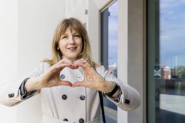 Madura mujer gesto corazón forma signo por la construcción - foto de stock