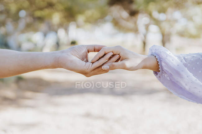 Boyfriend and girlfriend holding hands outdoors — Stock Photo