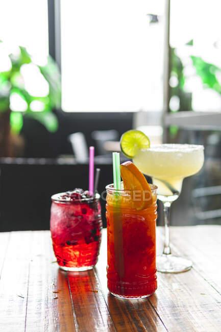 Copas decoradas de cócteles en la mesa en el bar - foto de stock